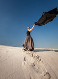 Woman in long dress holding long cloth on sand dune Stock Photo