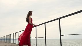 Woman in a long dress holds onto the railing near the sea, the wind blows hair. A young woman in a long scarlet dress holds onto the railing near the sea, her stock footage