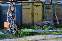Woman in a long dress with long flowing brown hair against the backdrop of abandoned warehouses Stock Photography