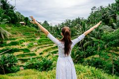 Woman in long dress looks on rice terrace view in Bali with raised hands. Indonesia Royalty Free Stock Images