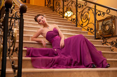 Woman in a long dress lying on the stairs. Young woman in a long dress lying on the stairs in the hotel lobby Royalty Free Stock Photography
