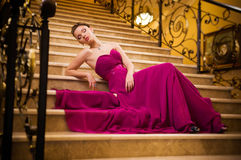 Woman in a long dress lying on the stairs Royalty Free Stock Image