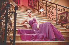 Woman in a long dress lying on the stairs Stock Photo