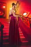 Woman in a long dress lying on the stairs Royalty Free Stock Photos