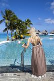 Woman in a long dress near the pool and palm trees. The woman in a long dress near the pool and palm trees Royalty Free Stock Photography