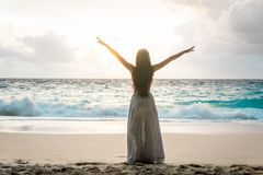 Woman in long dress with raised arms standing on beach and looking to ocean. Young woman in long dress with raised arms standing on beach and looking to ocean Stock Photography