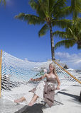 Woman in  long dress with a rose in  hand lies in a hammock on background of the sea Stock Images