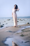 Woman in a long dress on the shore Stock Photography