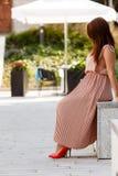 Woman in long dress sitting on city street Stock Photo