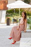 Woman in long dress sitting on city street Royalty Free Stock Images