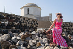 Woman in long dress  sitting on the stones near the Church Royalty Free Stock Photography
