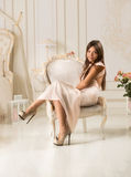 Woman in long dress sitting on white luxury chair at classic int Stock Image