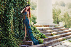 Woman in a long dress standing on the steps of the manor. Royalty Free Stock Photos