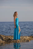 Woman in long dress on stony beach Royalty Free Stock Image
