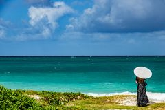 Woman in long dress with Umbrella overlooking the ocean royalty free stock photo