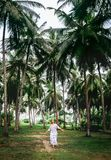 Woman in long dress walk under palm trees. Romantic island vacat. Ion Stock Image