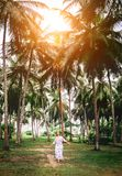 Woman in long dress walk under palm trees. Romantic island vacat. Ion Royalty Free Stock Image
