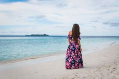 Woman in long dress walking on beach with pure water of ocean in Maldives. Woman in long dress walking on beach with pure blue water of ocean in Maldives Royalty Free Stock Photos