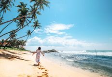 Woman in long dress walks on tropical island beach Royalty Free Stock Photos