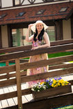 Woman in long dress and white hat walking on the old wooden brid Royalty Free Stock Photography