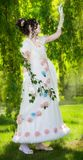 Woman in a long, elegant white bride dress in a park. Stock Image
