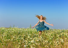 Woman with a long fair hair in a blue sundress joyfully moves in the field of camomiles against the blue sky Stock Images