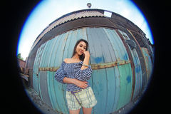 Woman with long flowing brown hair posing on a background of old rusty container,fisheye Stock Photo