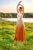 Woman in a long glamorous dress at sunset. Girl lovely gradient dress. Beautiful landscape view. Summer hot Fashions royalty free stock photography