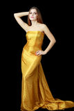 Woman in long golden dress Stock Images