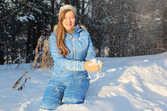 The woman with long hair in a blue jacket swept up by snow Stock Image
