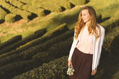 Woman with long hair with a bouquet of flowers of snowdrops on the background of a tea plantation royalty free stock images