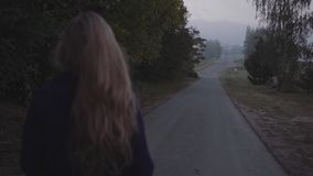 Woman walks on the road. Woman with long hair goes on the road in a purple coat close-up stock video footage