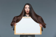 Woman with long hair holding blank board Royalty Free Stock Images