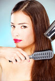 Woman with long hair holding blow dryer and comb Royalty Free Stock Photo