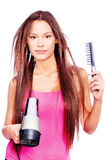 Woman with long hair holding blow dryer and comb Stock Image