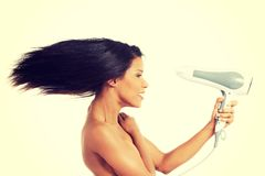 Woman with long hair holding blow dryer Royalty Free Stock Image