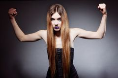 Woman long hair make-up shows her muscles Royalty Free Stock Photo