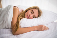 Woman with long hair sleeping on bed in bedroom Royalty Free Stock Photo