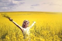 Woman with long hair standing on yellow rapeseed meadow with raised hands. Concept of freedom and happiness. Woman with long hair standing on yellow rapeseed royalty free stock photos