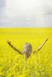 Woman with long hair standing on yellow rapeseed meadow with raised hands. Concept of freedom and happiness. royalty free stock photo