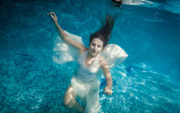 Woman with long hair swimming underwater at pool Stock Image