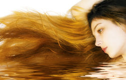 Woman with long hair in water. Portrait of woman with long and beautiful hair reflecting in water Stock Image