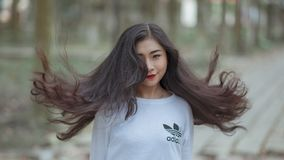 Woman With Long Hair Waving on Air and Wearing White Adidas Shirt Stock Photos