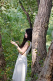 Woman with long hair wearing white dress, pose in the forest Royalty Free Stock Photography