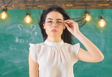 Woman with long hair in white blouse stands in classroom. Lady strict teacher on calm face stands in front of chalkboard. Strict teacher concept. Teacher with royalty free stock photography