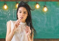Woman with long hair in white blouse stands in classroom. Lady strict teacher on dreamy face stands in front of. Chalkboard. Teacher with glasses and waving royalty free stock image