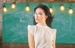 Woman with long hair in white blouse stands in classroom. Lady strict teacher on relaxed face stands in front of. Chalkboard. Teacher with glasses and waving stock photography