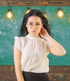Woman with long hair in white blouse stands in classroom. Lady strict teacher on relaxed face stands in front of. Chalkboard. teacher concept. Teacher with stock images