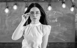 Woman with long hair in white blouse stands in classroom. Strict teacher concept. Teacher with glasses and waving hair. Looks attractive. Lady strict teacher on royalty free stock images