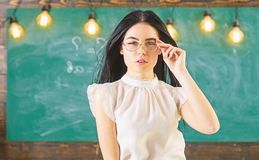 Woman with long hair in white blouse stands in classroom. Strict teacher concept. Teacher with glasses and waving hair. Looks attractive. Lady strict teacher on royalty free stock photo